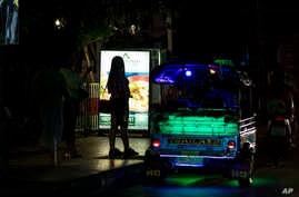 Sex workers stand in a largely shut-down red light area in Bangkok, Thailand, Thursday, March 26, 2020. A month-long state of…