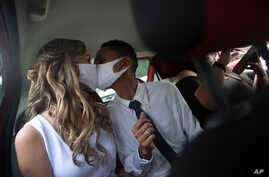 Wearing masks to prevent the spread of the new coronavirus, Thiago do Nascimento, right, and Keilla de Almeida kiss during…