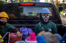 Construction workers wearing face masks travel in a back of a crew cab in Bangkok, Thailand, Wednesday, May 13, 2020. Thai…