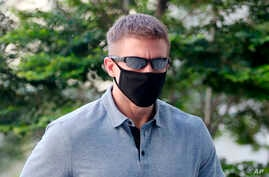 CORRECTS SOURCE - In this May 13, 2020, photo, Brian Dugan Yeargan, wearing a face mask and sunglasses, walks outside the…