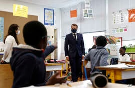 French President Emmanuel Macron, wearing a protective face mask, speaks with schoolchildren during a class at the Pierre…