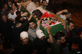 Muslim men carry the body of Iyad Halak to burial after Israeli police shot him dead in Jerusalem's old city, Sunday, May 31,…