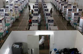 Health workers perform testing at a COVID-19 testing center at the Palacio de Manila during an enhanced community quarantine to…
