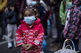 A young girl wearing a mask to prevent the spread of the coronavirus, looks on after refugees and migrants arrived at the port…
