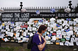 A woman passes a fence outside Brooklyn's Green-Wood Cemetery adorned with tributes to victims of COVID-19, Thursday, May 28,…