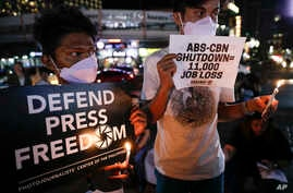 Protesters light candles while they hold banners, during a rally in metropolitan Manila, Philippines, Monday, Feb. 10, 2020…