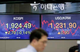 A currency trader walks near the screens showing the Korea Composite Stock Price Index (KOSPI), left, and the foreign exchange…