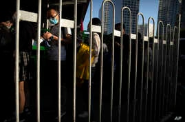 Commuters wearing face masks to protect against the new coronavirus wait in line for buses in the central business district in…
