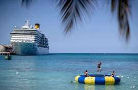 A cruise ship sits docked as tourists jump on a trampoline in Ocho Rios, Jamaica, Friday, Feb. 15, 2019. (AP Photo/David…