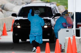 In this Friday, May 1, 2020, photo, a medical worker directs a local resident at a drive-thru COVID-19 testing site in Waterloo…