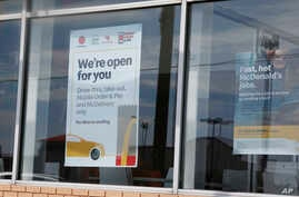 A sign in the window at a McDonald's restaurant states no dine-in seating Thursday, May 7, 2020, in Oklahoma City, where three…