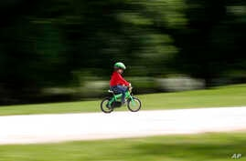A child rides a bicycle in a park which reopened after several weeks of closure, in Milan, Italy, Monday, May 4, 2020. Italy…