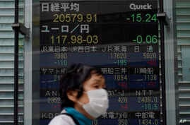 A masked woman walks past an electronic stock board showing Japan's Nikkei 225 index at a securities firm in Tokyo Thursday,…
