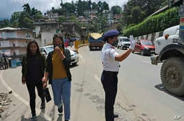 A traffic policewoman wearing a face mask controls the flow of traffic in Kohima, capital of the northeastern Indian state of…