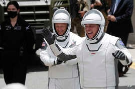 NASA astronauts Douglas Hurley, left, and Robert Behnken wave as they walk out of the Neil A. Armstrong Operations and Checkout…