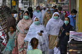 A family wearing masks to help curb the spread of the coronavirus visits a market in Rawalpindi, Pakistan, Tuesday, June 2,…