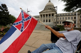 Larry Eubanks of Star waves the current Mississippi state flag as he sits before the front of the Capitol, Saturday, June 27,…