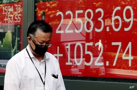 A man walks past an electronic stock board showing Japan's Nikkei 225 index at a securities firm in Tokyo, Tuesday, June 16,…