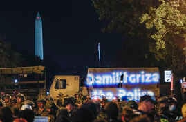 Demonstrators project the words 'demilitarize the police' onto a military vehicle as protests continue over the death of George…