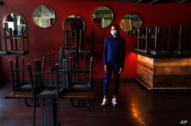 In this Thursday, May 21, 2020, image, Stephanie Byrd, co-owner of The Block, poses for a photo with chairs on the tables while…