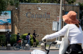 A security guard stands on duty as residents pass by the Canadian Embassy in Beijing on Friday, June 19, 2020. Chinese…