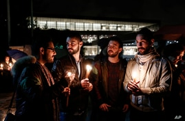 Demonstrators hold candles during a gathering in front of the Acropolis museum at the foot of the Acropolis hill in Athens,…