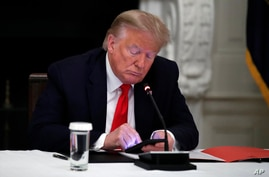 President Donald Trump looks at his phone during a roundtable with governors on the reopening of America's small businesses, in…