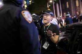 """Associated Press videojournalist Robert Bumsted reminds a police officer that the press are considered """"essential workers"""" and…"""