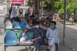 People sit in waiting area of the Benazir Hospital ignore social distancing, during a lockdown to contain the spread of…