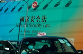 A taxi drives past a big banner featuring the Hong Kong National Security Law in Hong Kong, Monday, June 29, 2020. China's…