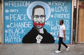 A man walks past a mural depicting George Floyd during a protest over the death of Floyd Sunday, May 31, 2020, in Los Angeles…