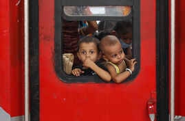 In this Saturday, May 30, 2020 photo, Indian migrant worker's children peer out from the window of their train in Prayagraj,…