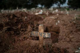 A cross marks the grave of 57-year-old Paulo Jose da Silva, who died from the new coronavirus, in Rio de Janeiro, Brazil,…