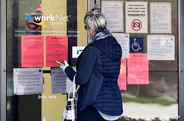 A woman checks job application information in front of IDES(Illinois Department of Employment Security)/WorkNet center in…