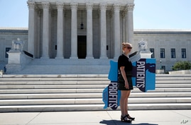 An anti-abortion protester stands outside the Supreme Court on Capitol Hill in Washington, Monday, June 29, 2020.  The Supreme…