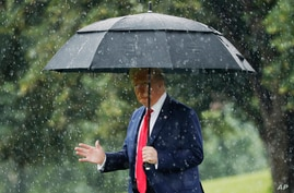 President Donald Trump walks in the rain on the South Lawn of the White House in Washington, Thursday, June 11, 2020, before…