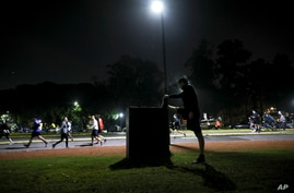A man stretches as people exercise at a park in Buenos Aires, Argentina, Monday, June 8, 2020. The city government authorized…