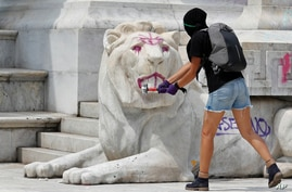 A woman hits a statue of a lion with a sledgehammer as protestors angry at the police attack the monument to Mexico's first…