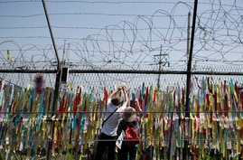 Visitors hang a ribbon on a wire fence decorated with other ribbons at the Imjingak Pavilion in Paju, South Korea, Tuesday,…