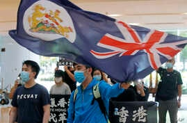 A protester waves a Hong Kong colonial flag in a shopping mall during a protest in Hong Kong, Friday, June 12, 2020. Protesters…