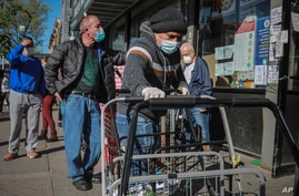 A masked grocery store worker in Brooklyn's Sunset Park—a neighborhood with one of the city's largest Mexican and Hispanic…