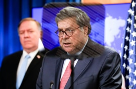 Attorney General William Barr speaks from behind a teleprompter as Secretary of State Mike Pompeo listens, during a joint…
