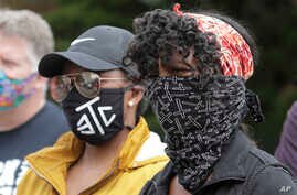 Protesters wear masks to help prevent the spread of the coronavirus, Friday, June 5, 2020, in Tacoma, Wash., during a protest…