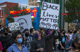 Demonstrators protest the death of George Floyd in downtown Albuquerque, N.M., Sunday, May 31, 2020. Floyd was a black man who…