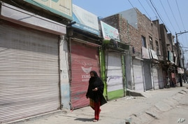 A woman walks past shops that are closed due to an escalation of cases of the coronavirus in Peshawar, Pakistan, Wednesday,…