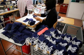 In this Friday, June 12, 2020 photo, an employee sews face protective masks in Chanteclair Hosiery, a French knitwear clothing…