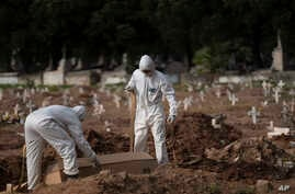 Cemetery workers in protective clothing maneuver the coffin of 57-year-old Paulo Jose da Silva, who died from the new…