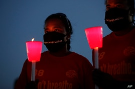 Kourtni Abner, left, and Kimberly Johnson, right, take part in a candle light vigil to honor George Floyd in Houston, Monday,…