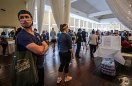 Voters wait in line to cast their ballots in the state's primary election at a polling place, June 9, 2020, in Atlanta.