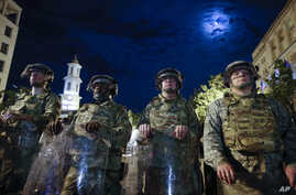 Utah National Guard soldiers stand on a police line as demonstrators gather to protest the death of George Floyd, Thursday,…